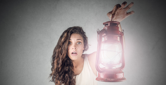 dark haired girl wearing a white dress and holding a lantern