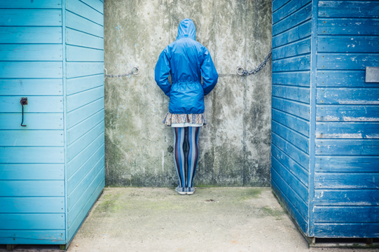 A person is standing with their head against the wall in between two beach huts